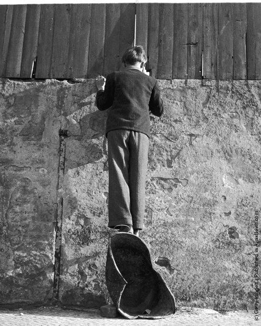 Мальчик в Берлине сквозь щель в стене следит за футбольным матчем в Западном Берлине