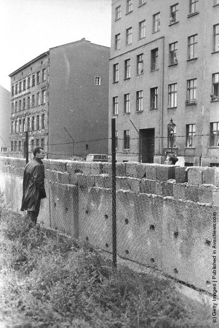 Житель Восточного Берлина смотрит через стену на Западный Берлин