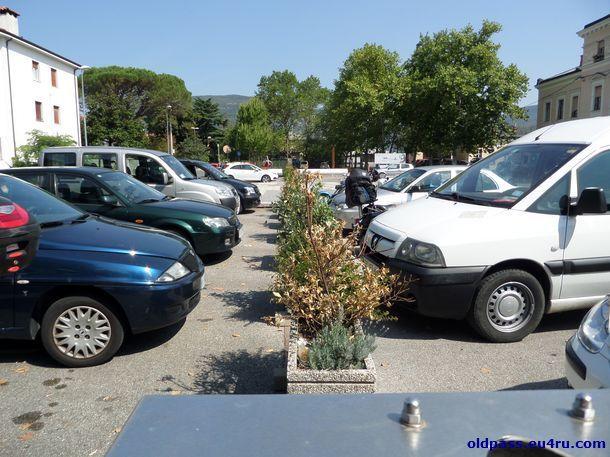 Бесплатный паркинг на площади. Слева машины стоят в Италии, справа - в Словении.
