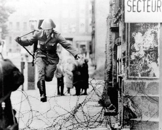 Этот снимок обошел весь мир. Солдат национальной народной армии ГДР бросает оружие и прыгает через спираль